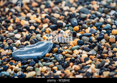 Abstract background with decorative floor pattern of sea gravel stones, Gravel texture with selective focus.