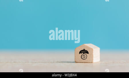 Real Estate and Housing Property Market Concept using Wooden House Model on Blue Background - Stock Photo