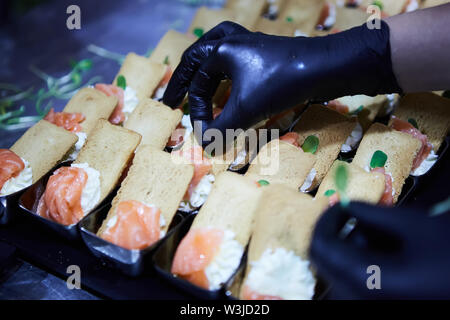 Chef making Norwegian Smoked Salmon Canapes with Cream Cheese - Stock Photo
