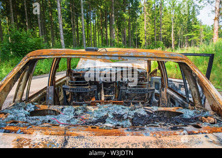 Interior of a burned out car from behind at the roadside - Stock Photo