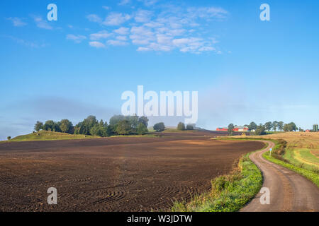 Agricultural land view with a winding country road - Stock Photo