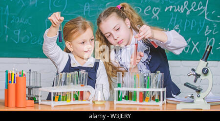 Chemistry is about reaction. Smart school children performing chemistry test in lab. Small schoolgirls learning chemistry during school time. Little pupils holding test tubes in chemistry laboratory. - Stock Photo