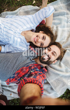 Image of laughing couple man and woman dressed in casual taking selfie photo while lying in green park - Stock Photo