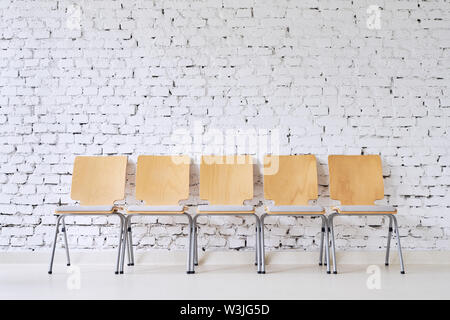 Row of five empty modern chairs in front of stylish brick wall