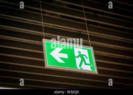 Emergency fire exit sign glowing green in the blacked out background at airport - Stock Photo