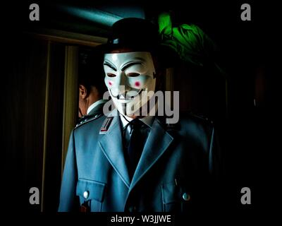 german soldier in uniform with guy fawkes mask on the face - Stock Photo