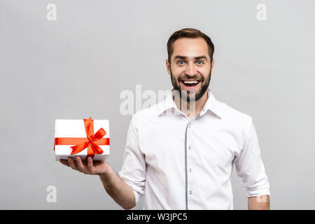 Portrait of a handsome young businessman wearing white shirt and tie standing isolated over gray background, showing gift box - Stock Photo