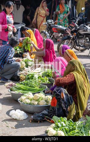 PUSHKAR, INDIA - NOVEMBER 17, 2018 : Food trader selling vegetables in the street market in holy city Pushkar, Rajasthan, India - Stock Photo