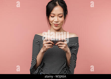 Photo of cute asian woman dressed in basic wear smiling and holding smartphone isolated over red background in studio - Stock Photo