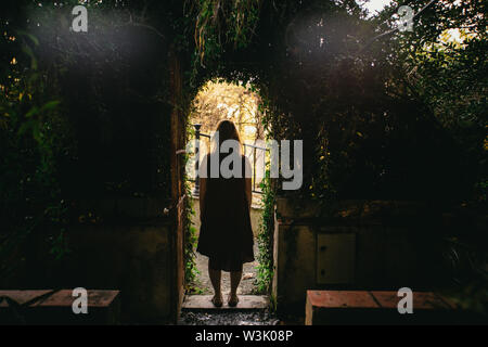 Woman standing framed in an arched doorway covered in leafy green foliage in the La Concepcion Historical-Botanical Garden, Malaga, Spain - Stock Photo