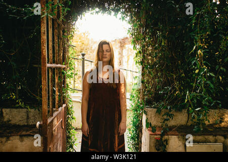Spiritual young woman standing meditating in the arched door of the cycad greenhouse in the La Concepcion Historical-Botanical Garden, Malaga, Spain - Stock Photo