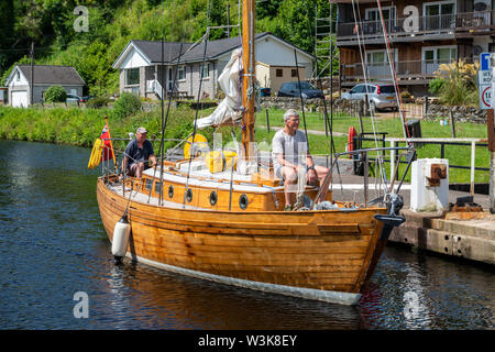 Wooden yacht approaching lock 8 at Cairnbaan on Crinan Canal, Argyll and Bute, Scotland, UK - Stock Photo