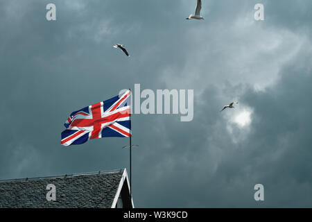 British flag fluttering in the wind on the roof of a house amid clouds and flying seagulls - Stock Photo