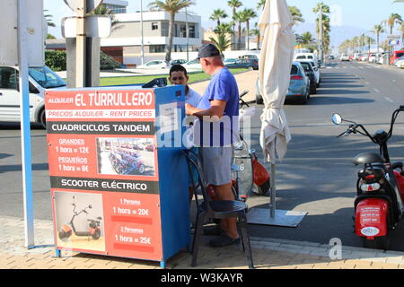 Place of leisure with tandem quadricycles and electric scooter in the Urbanization of Roquetas de Mar of Almería in Spain on july 14, 2019 - Stock Photo