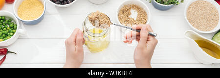 cropped view of woman adding couscous in jar with oil on wooden white table, panoramic shot - Stock Photo