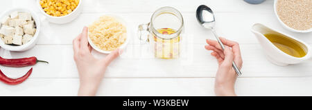 cropped view of woman holding bowl with couscous near glass jar on wooden white table, panoramic shot - Stock Photo