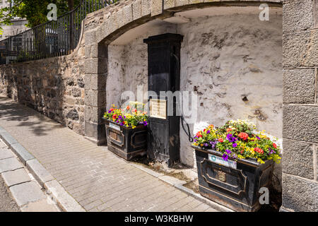 Floral displays beside an old public water pump dated 1918 in The Pollett under La Plaiderie, St Peter Port, Guernsey, Channel Islands UK