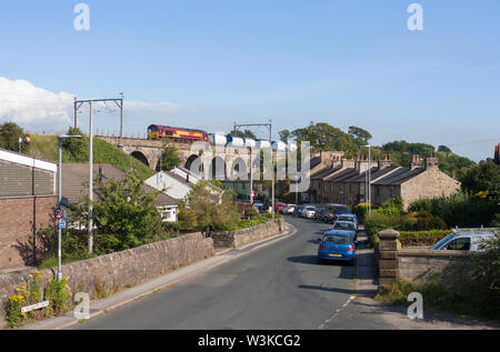 DB cargo class 66 locomotive crossing the viaduct at Galgate on the west coast mainline with a intermodal containter freight train - Stock Photo