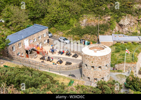 Looking down from the coastal path onto the tearooms and the Napoleonic loophole tower overlooking Petit Bot Bay, Guernsey, Channel Islands UK - Stock Photo