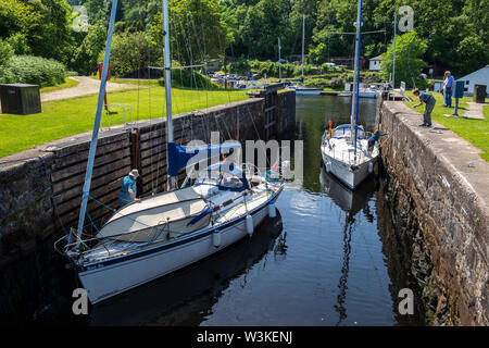 Two yachts manoeuvre into position within lock 14 at Crinan Basin on Crinan Canal, Argyll and Bute, Scotland, UK - Stock Photo