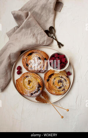 Top view of delightful french breakfast with cinnamon and raisins rolls and fresh raspberries on flat white surface. - Stock Photo