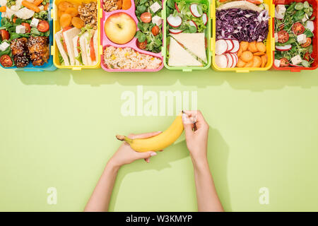 cropped view of woman holding banana in hands near lunch boxes with food - Stock Photo