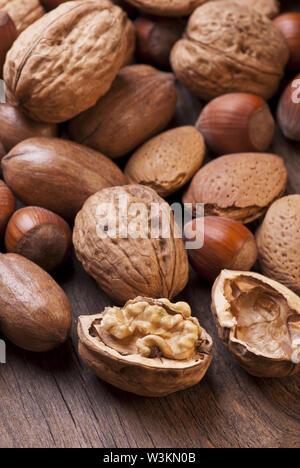closeup of different types of dried fruit including pecans, almonds and hazelnuts in shell on rustic wooden table - Stock Photo