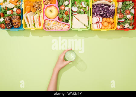 cropped view of woman holding glass of water in hand near lunch boxes with food - Stock Photo
