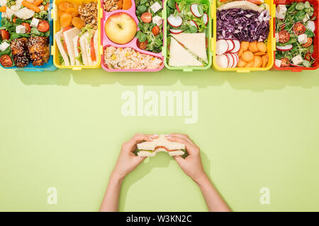 cropped view of woman holding sandwich in hands near lunch boxes with food - Stock Photo