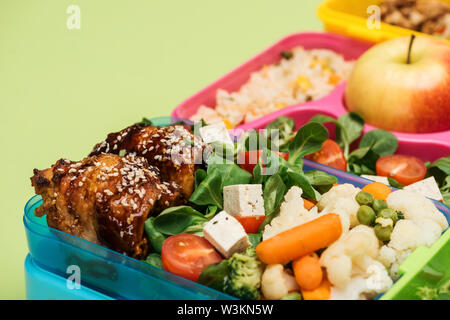 close up view of meal in lunch boxes isolated on green - Stock Photo