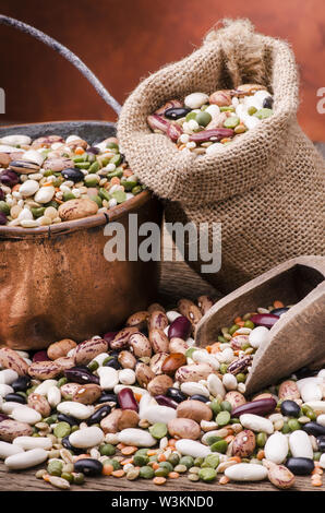 legumes and dried cereals mixed in a copper pot and a bag of yuta on rustic wooden table.still life - Stock Photo