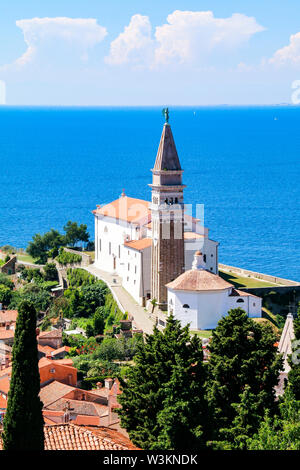 View of St George's Church and the red tiled rooftops of the old town of Piran in Slovenia, with the Adriatic Sea in the background - Stock Photo