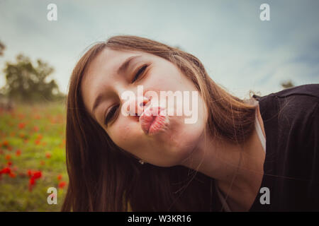 Young woman making duckface kiss while taking selfie picture with her smartphone or camera in field of red poppies. She having fun doing silly and fun - Stock Photo