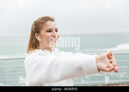 Image of young fitness woman 20s in white hoodie smiling and stretching her arms while doing workout near seaside - Stock Photo