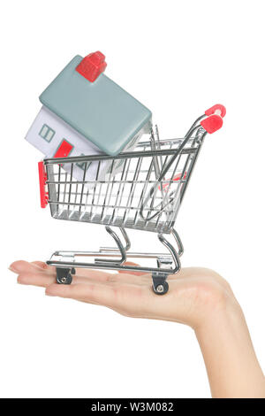 House and home for sale in shopping cart concept. Hand showing mini model house in miniature shopping cart. Buying new house, real estate and home mortgage conceptual image isolated, white background.