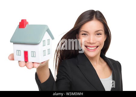 Real estate agent selling home holding mini house. Female realtor in business suit smiling happy showing model house isolated on white background. Multiracial Caucasian / Chinese Asian woman agent. - Stock Photo