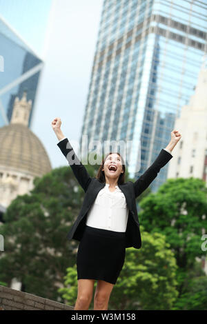 Business achievements success businesswoman in Hong Kong celebrating business goals with arms raised up as winner. Young mixed race Chinese Asian / Caucasian female professional in Hong Kong central. - Stock Photo