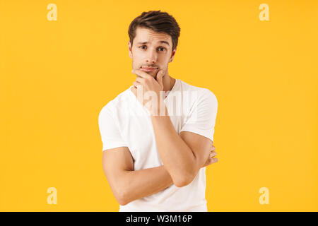 Photo of attractive man in basic t-shirt touching his chin and looking at camera with pensive face isolated over yellow background - Stock Photo
