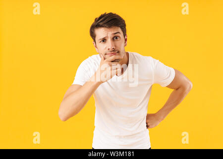 Photo of thoughtful man in basic t-shirt touching his chin and looking at camera with pensive face isolated over yellow background - Stock Photo