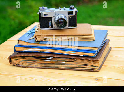 Old photo albums old camera on a light wooden table in the summer garden.