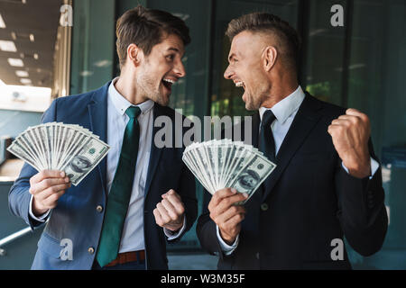 Image of happy businessmen partners dressed in formal suit rejoicing and holding bunch of cash money while standing outside office center - Stock Photo