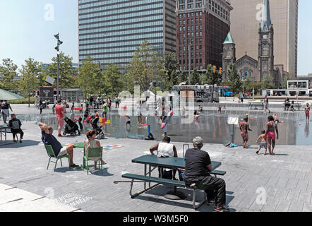 Public Square in downtown Cleveland Ohio is a magnet on hot summer days where people can cool of in the public water fountains. - Stock Photo