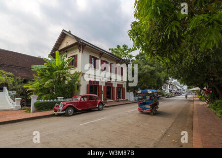 Old Citroen car parked in front of an old French colonial building and little traffic on the idyllic Sakkaline Road in Luang Prabang in the morning. - Stock Photo