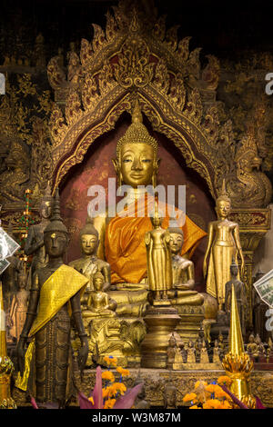Altar with many golden Buddha statues at a Buddhist temple in Luang Prabang, Laos. - Stock Photo