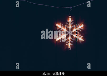 Electric star hanging outside wooden home during Christmas in winter - Stock Photo