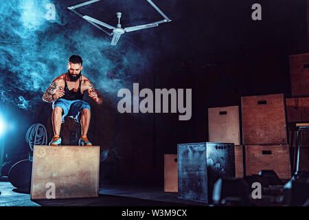Fit tattoed bearded man jumping onto a box as part of exercise routine. Man doing box jump in the gym. Athlete is performing box jumps. - Stock Photo