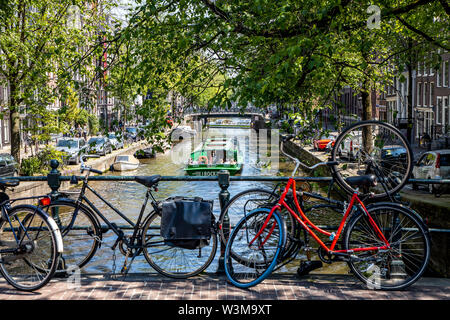 Amsterdam, Netherlands, downtown, old town, wheels, parked on a railing of a bridge over a canal, - Stock Photo