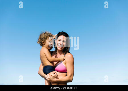 Mother carrying her son wearing swimwear - Stock Photo