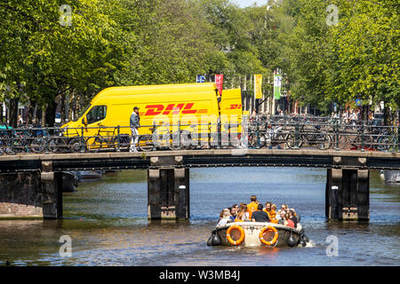 Amsterdam, Netherlands, downtown, old town, DHL courier vehicle, delivers parcels, on a bridge over a canal,