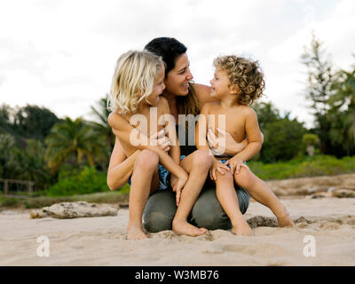 Woman with her sons sitting on her lap on beach - Stock Photo